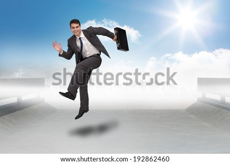 Smiling businessman in a hurry against cityscape on the horizon