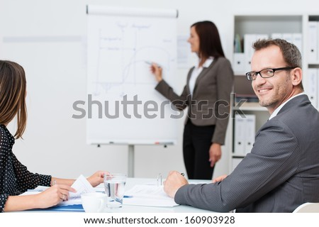 Smiling businessman in a meeting or lecture at the office turning to look at the camera while a businesswoman gives a presentation in the background - stock photo