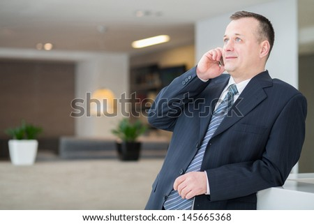 Smiling businessman in a suit and tie talking on the phone