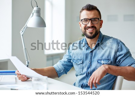 Smiling businessman in denim shirt and eyeglasses looking at camera in office - stock photo