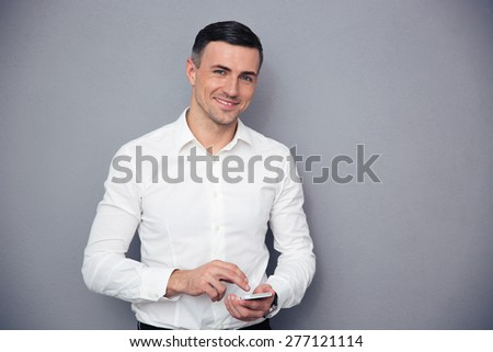 Smiling businessman in formal wear using smartphone over gray background. Looking at camera - stock photo