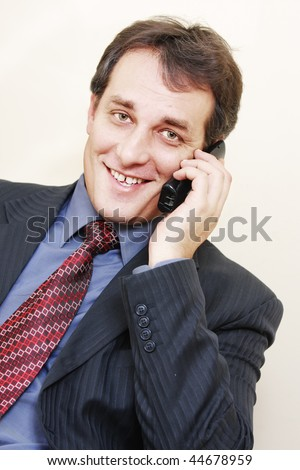 Smiling businessman in formal wear with phone inclining left - stock photo