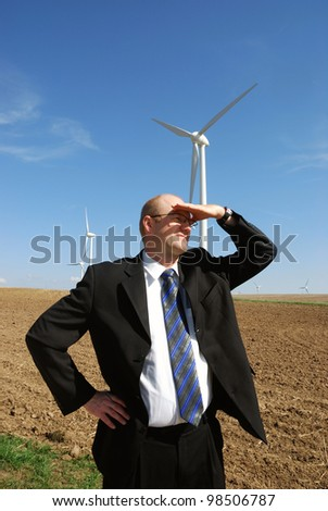 smiling businessman in front of a wind turbine