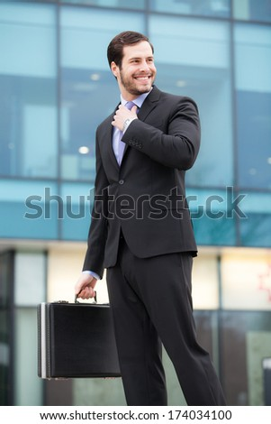 smiling businessman in front of an office building with a briefcase  - stock photo