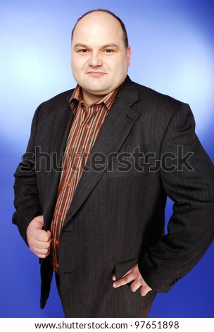 smiling businessman in front of blue background - stock photo