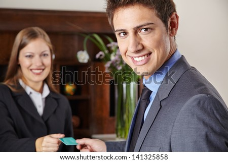 Smiling businessman in hotel getting his key card at the reception - stock photo
