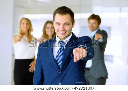 Smiling businessman  in office with colleagues in the background. Pointing by finger into the camera