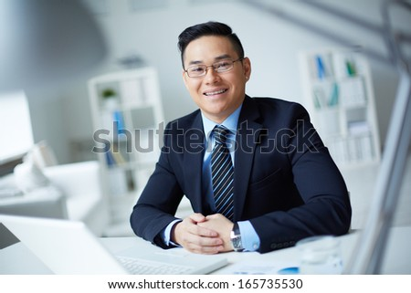 Smiling businessman in suit looking at camera in office - stock photo