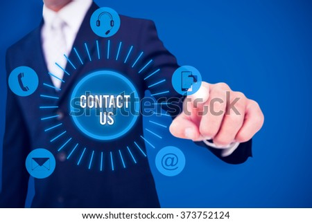 Smiling businessman in suit pointing against royal blue - stock photo