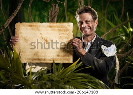 Smiling businessman in the jungle holding an old stained parchment. - stock photo