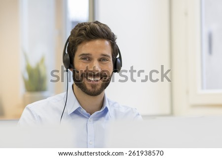 Smiling Businessman in the office on the phone, headset, Skype. looking camera - stock photo