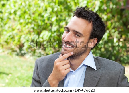 Smiling businessman in the park  - stock photo