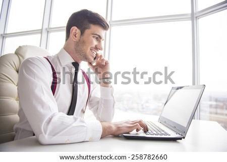 Smiling  businessman is working on his laptop in his office and is speaking phone.