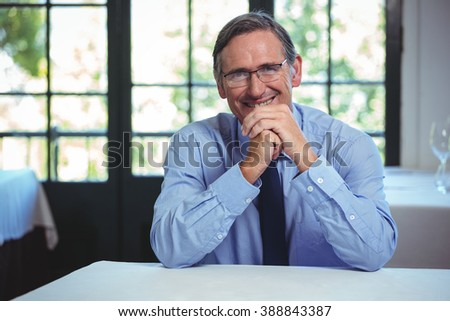 Smiling businessman leaning on a table in a restaurant