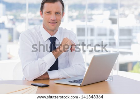 Smiling businessman leaning on his desk in his office - stock photo