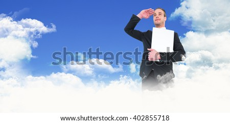 Smiling businessman looking and holding laptop against scenic view of blue sky
