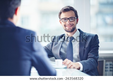 Smiling businessman looking at camera during coffee break with his colleague - stock photo
