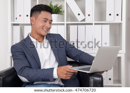 Smiling businessman looking at his laptop screen while sitting in large leather armchair in office. Concept of successful business