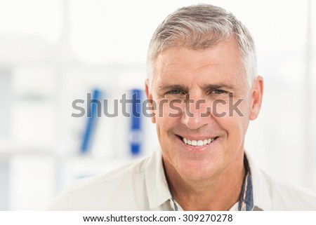 Smiling businessman looking at the camera in the office