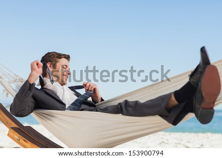 Smiling businessman lying in hammock taking off his tie at beach - stock photo