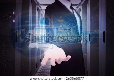 Smiling businessman offering something with his open hand against data center