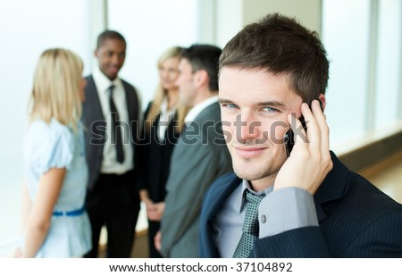 Smiling businessman on phone in office with his team in the background