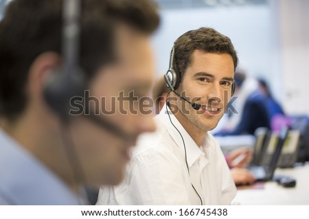 Smiling Businessman on the phone with headset, office background, looking camera - stock photo