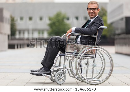 Smiling businessman on wheelchair  - stock photo