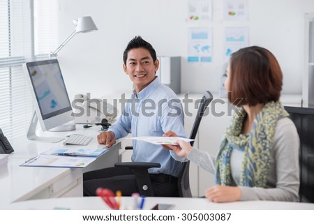 Smiling businessman passing financial document to his female colleague