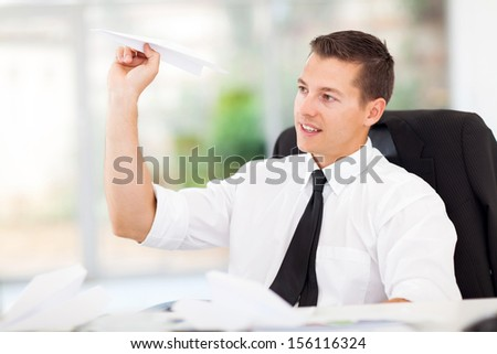 smiling businessman playing with paper airplane in office