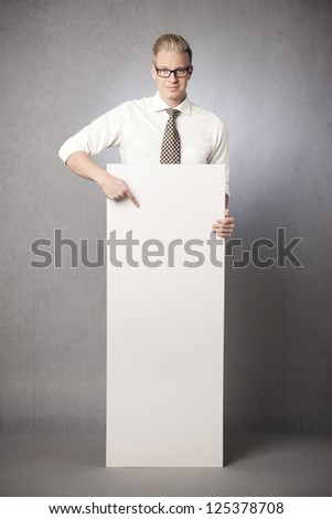Smiling businessman pointing finger at white empty vertical panel with space for text isolated on grey background. - stock photo