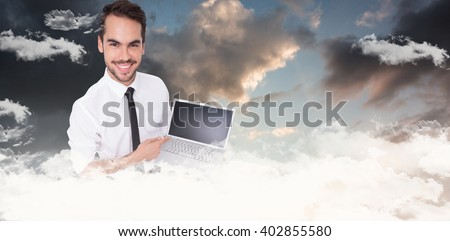 Smiling businessman pointing his laptop against blue and orange sky with clouds - stock photo