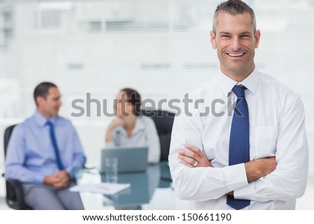 Smiling businessman posing crossing arms in bright office - stock photo