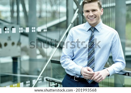 Smiling businessman posing smartly - stock photo