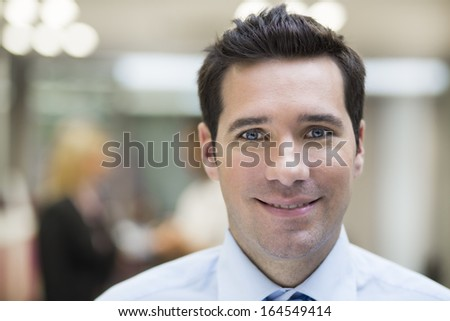 Smiling Businessman posing while colleagues talking together in office - stock photo