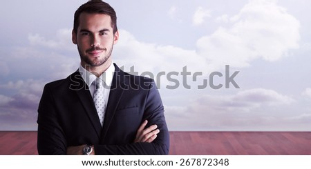 Smiling businessman posing with arms crossed against clouds in a room - stock photo