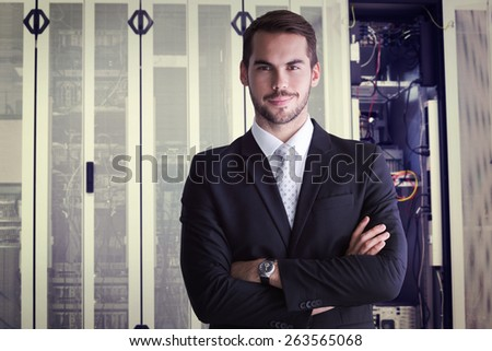 Smiling businessman posing with arms crossed against data center - stock photo