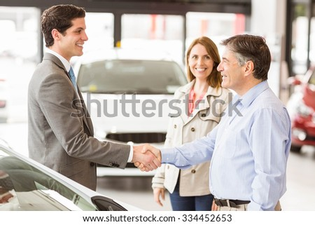Smiling businessman presenting a car at new car showroom