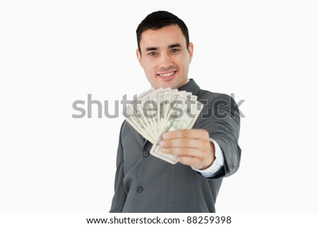 Smiling businessman presenting bank notes against a white background - stock photo