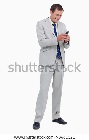 Smiling businessman reading text message against a white background - stock photo