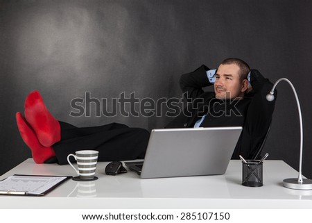 Smiling businessman relaxing with feet over up his desk - stock photo