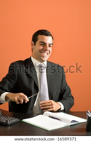 Smiling businessman seated at his computer pretending to cut his tie with scissors. Vertically framed photo. - stock photo