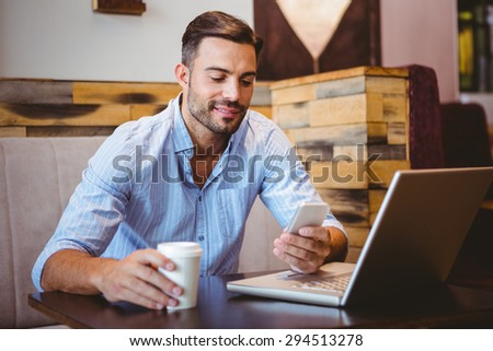 Smiling businessman sending a text message with laptop beside at the cafe - stock photo