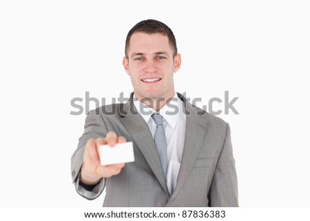 Smiling businessman showing a blank business card against a white background - stock photo
