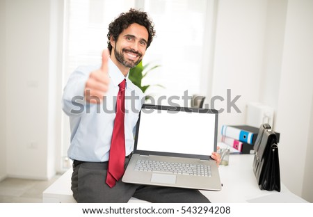 Smiling businessman showing a laptop with a blank screen