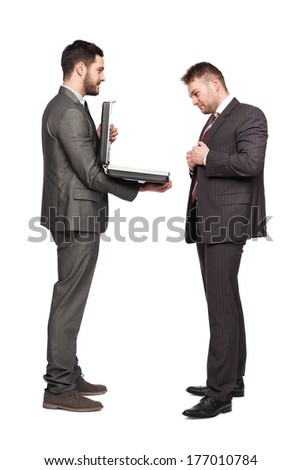 smiling businessman showing briefcase to an elegant man on white bacground