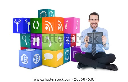 Smiling businessman showing his digital tablet against app cube - stock photo