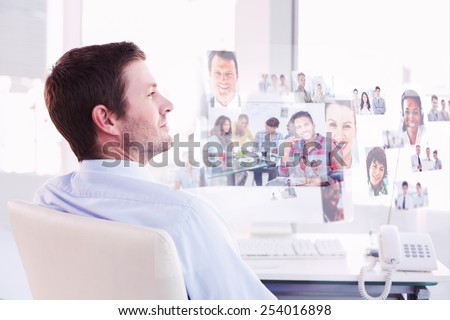 Smiling businessman sitting at his desk against handsome designer sit in his office - stock photo