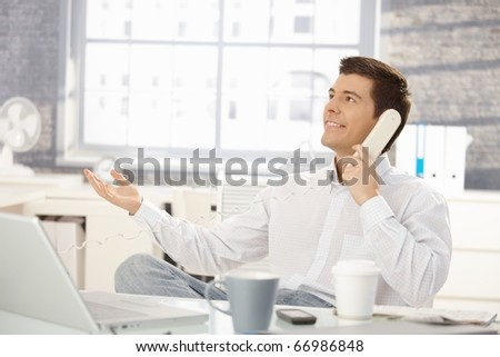 Smiling businessman sitting at office desk on landline phone call, looking up, raising hand.? - stock photo