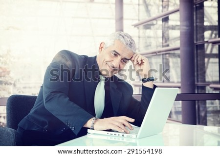 Smiling businessman sitting at office desk working with laptop.